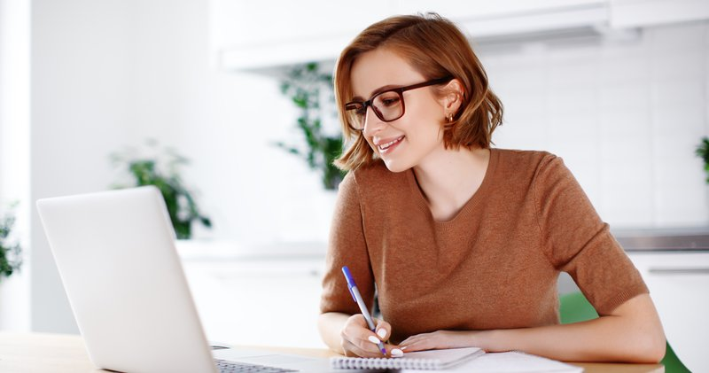 Young woman taking notes in front of a laptop